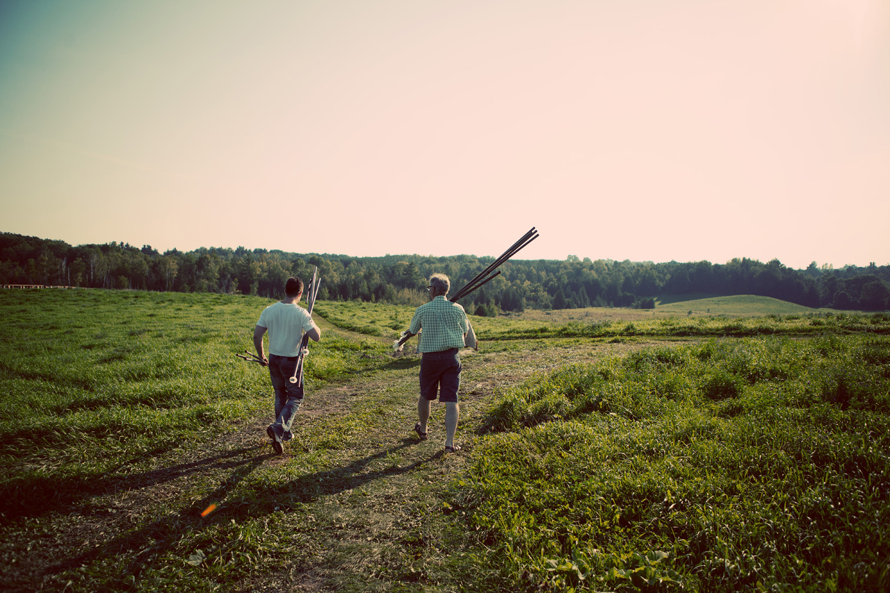men carrying poles in the field