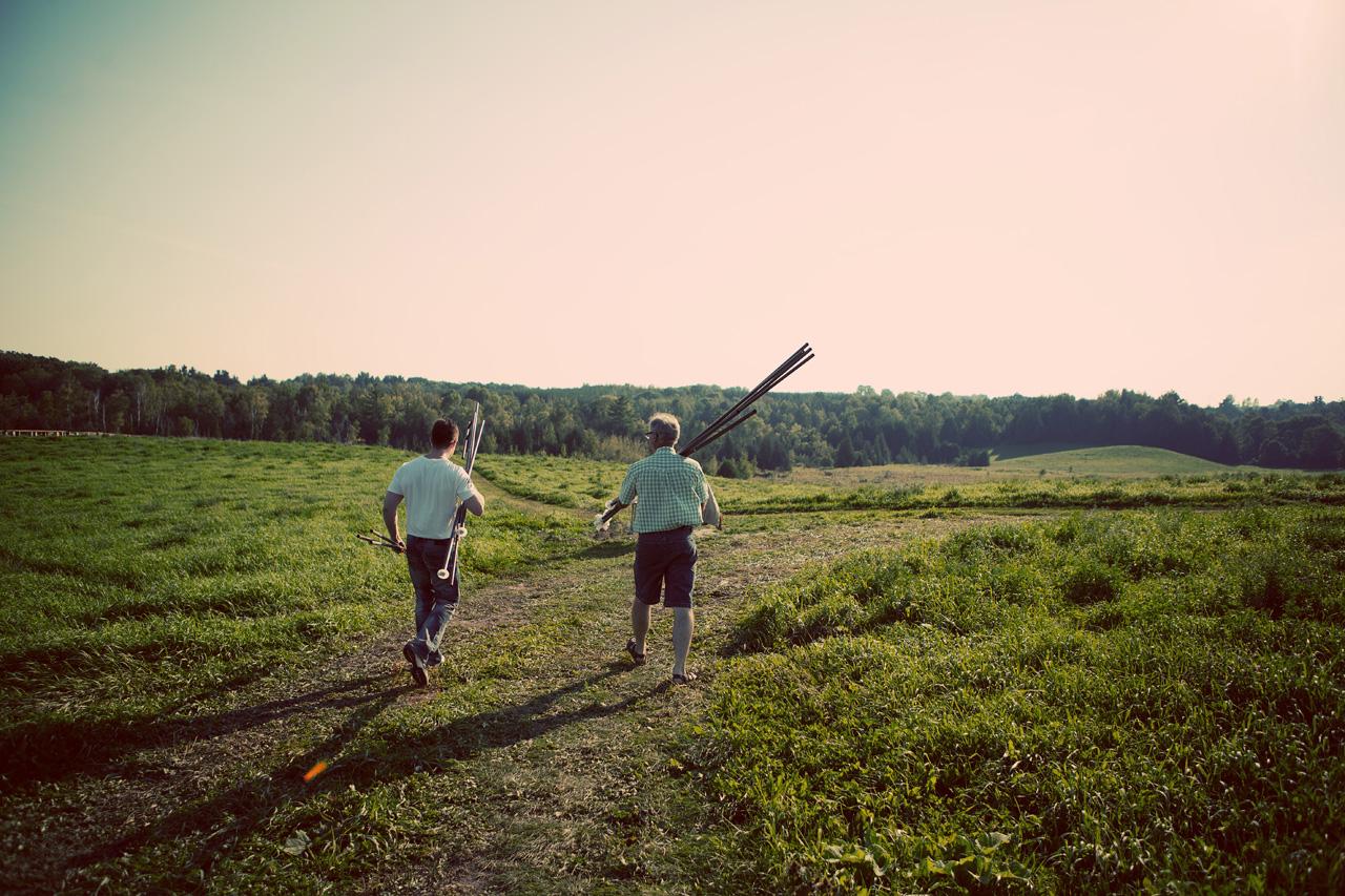men carrying poles in the field